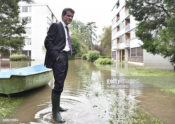 French Prime Minister Manuel Valls wearing boots visits flooded areas in BoussySaintAntoine on June 4 2016 in a southern Paris' suburb The...