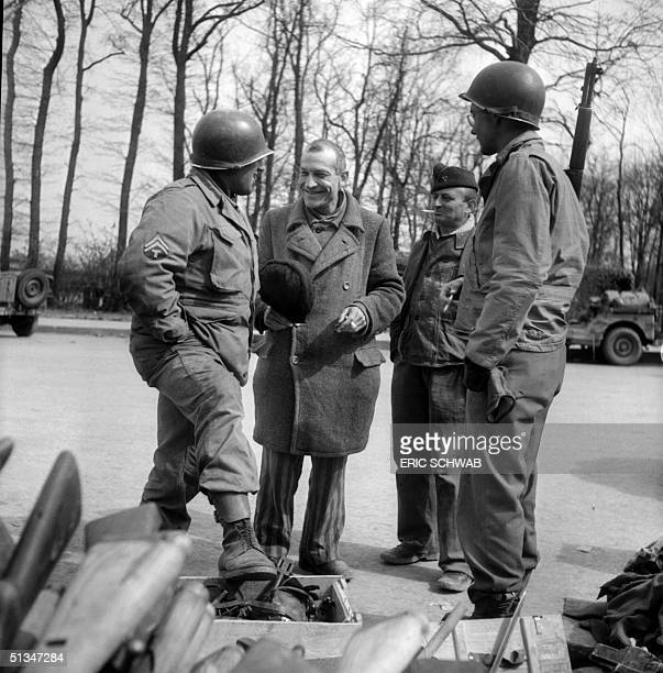 French prisoner commandant Bellon chats with American soldiers in front of a pile of arms in the courtyard of Nazi camp of Buchenwald in April 1945...