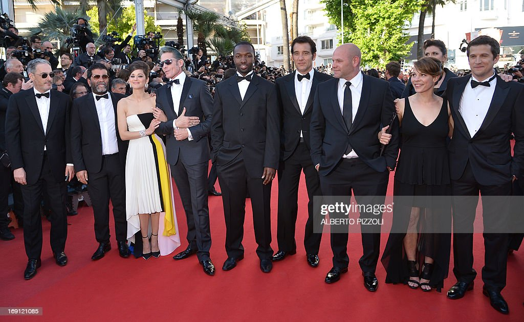 French producer Alain Attal, French actress Marion Cotillard, US tattoo artist and actor Mark Mahoney, US actor Jamie Hector, British actor Clive Owen, US actor Domenick Lombardozzi, US actress Lili Taylor and French director Guillaume Canet pose on May 20, 2013 as they arrive for the screening of the film 'Blood Ties' presented Out of Competition at the 66th edition of the Cannes Film Festival in Cannes. Cannes, one of the world's top film festivals, opened on May 15 and will climax on May 26 with awards selected by a jury headed this year by Hollywood legend Steven Spielberg. AFP PHOTO / ALBERTO PIZZOLI