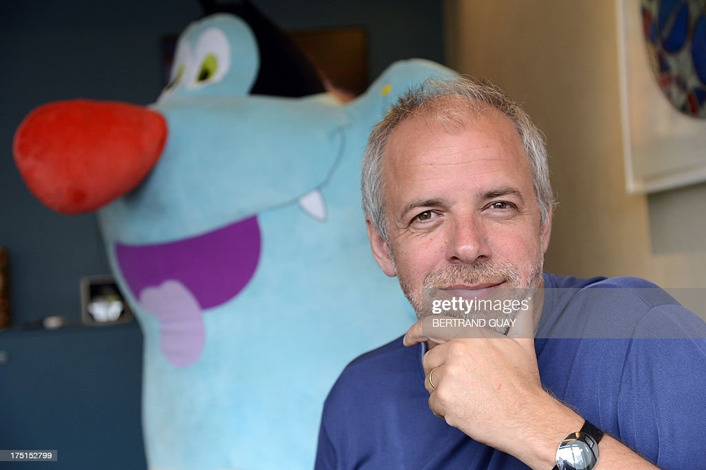 French producer Marc du Pontavice poses in front of the TV animation character Oggy of 'Oggy and the Cockroaches' on July 30, 2013 in Paris. TV animation series 'Oggy and the Cockroaches' is produced by French animation company Xilam, established in 1999 by Marc du Pontavice, and will be released on August 7 into a film directed by Olivier Jean-Marie. AFP PHOTO BERTRAND GUAY