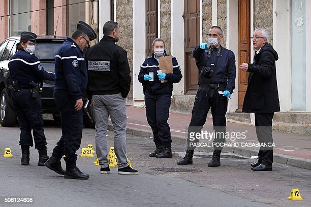 French prosecutor Eric Bouillard and police officres looks for evidence near a Muslim butcher's shop that was sprayed with bullets overnight on...