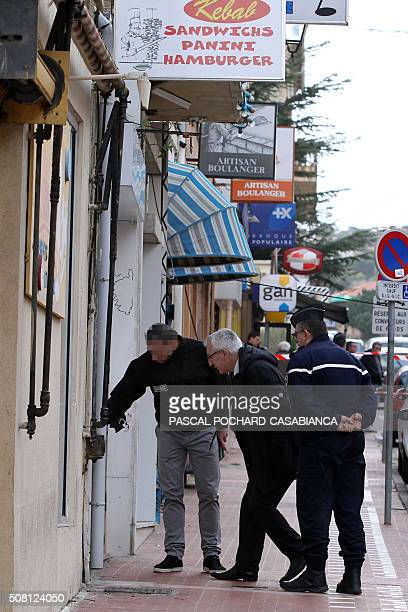 French prosecutor Eric Bouillard looks at evidence at a Muslim butcher's shop that was sprayed with bullets overnight on February 3 2016 in Propriano...