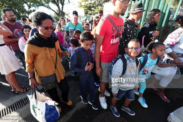 French pupils are accompanied by their parents to Michel Debre elementary school on the first day of the new school year in SaintDenis de la Reunion...