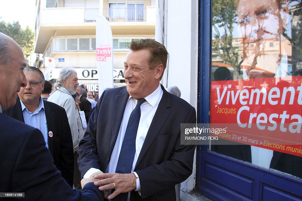 French Pyrenees-Orientales Socialist Party (PS) member of parliament Jacques Cresta (R) shakes a hand as he presents his candidacy for the 2014 mayoral elections in Perpignan during the inauguration of his campaign headquarters on October 26, 2013 in Perpignan. AFP PHOTO / RAYMOND
