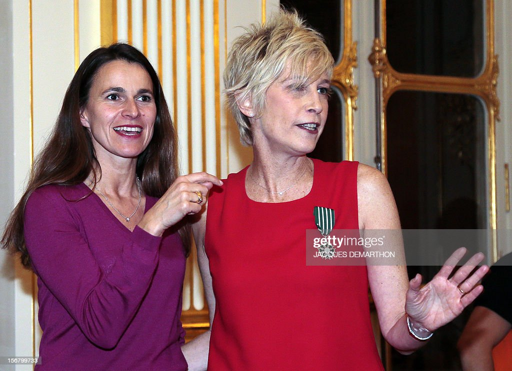 French radio host and former singer Valli (R) poses on November 21, 2012 with French Culture Minister Aurelie Filippetti after receiving the knight of the Order of Arts award during a ceremony at the Culture Ministry in Paris.