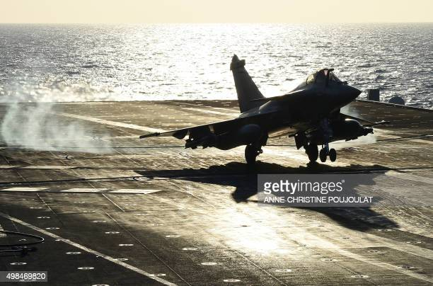 A French Rafale fighter aircraft lands aboard the French CharlesdeGaulle aircraft carrier after a flight on November 23 2015 at eastern Mediterranean...