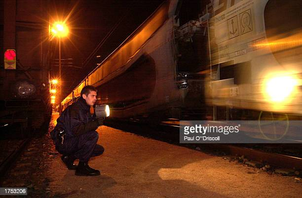 A French Railway police official searches a freight train for asylum seekers June 13 2002 at Calais France The officials are looking for asylum...
