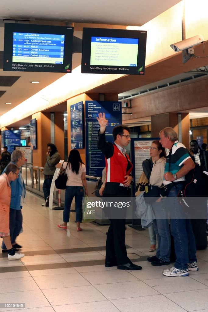 A French railways company SNCF Assistance employee (C) gives informations to people, on September 17, 2012, at the Gare du Nord railway station in Paris, after RER commuting trains were blocked for several hours due to an unexpected temporary strike of some SNCF agents.