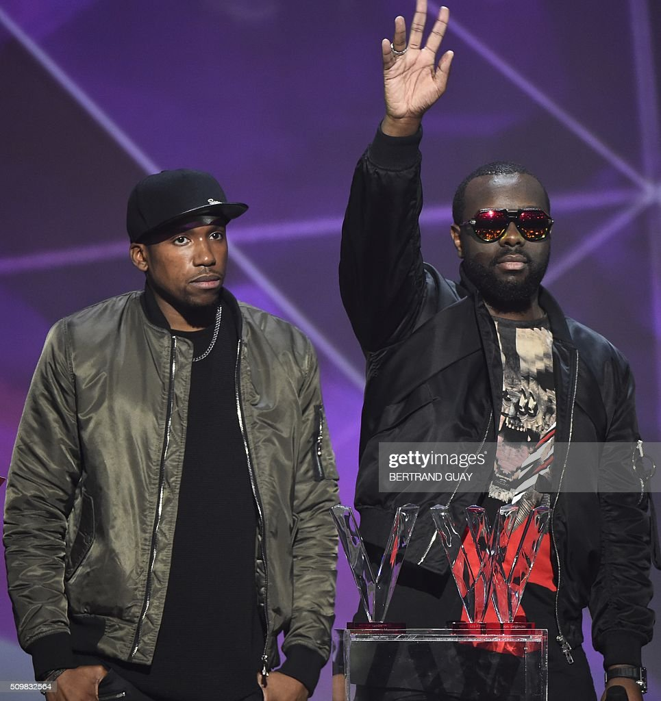 French rapper Gandhi Djuna aka Maitre Gims (R) gestures after receiving the best song award during the 31st Victoires de la Musique, the annual French music awards ceremony, on February 12, 2016 at the Zenith concert hall in Paris. AFP PHOTO / BERTRAND GUAY / AFP / BERTRAND GUAY