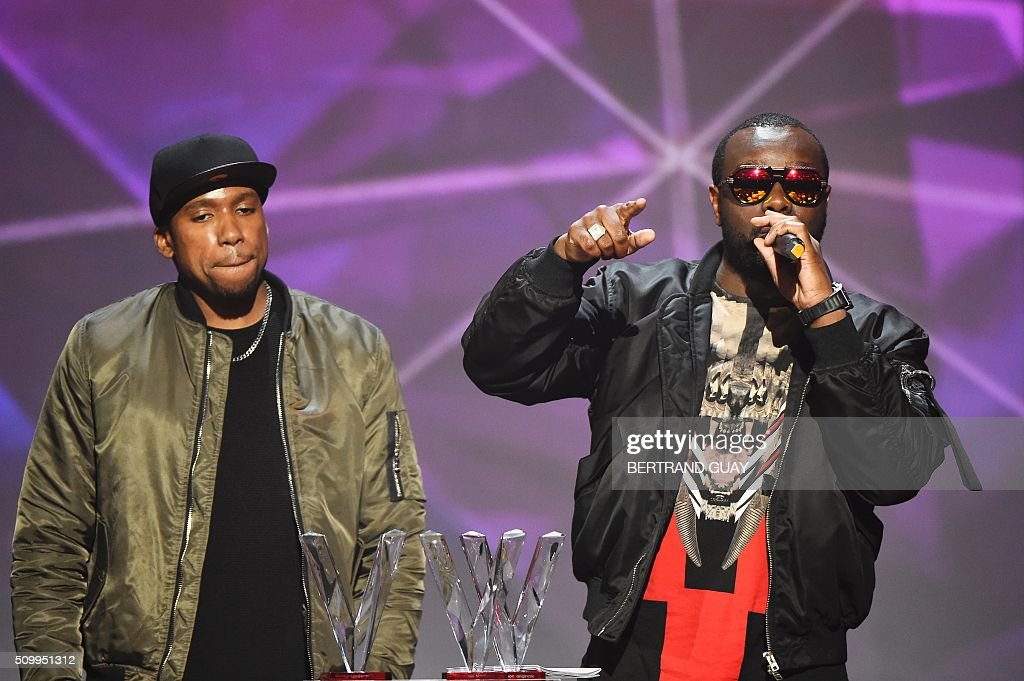 French rapper Gandhi Djuna aka Maitre Gims (R) gestures after receiving the best song award during the 31st Victoires de la Musique, the annual French music awards ceremony, on February 12, 2016 at the Zenith concert hall in Paris. / AFP / BERTRAND GUAY