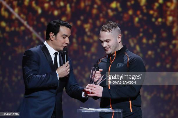 French rapper Julien Marie aka Jul reacts as he receives the best urban music album award from French TV host Thomas Thouroude during the 32nd...