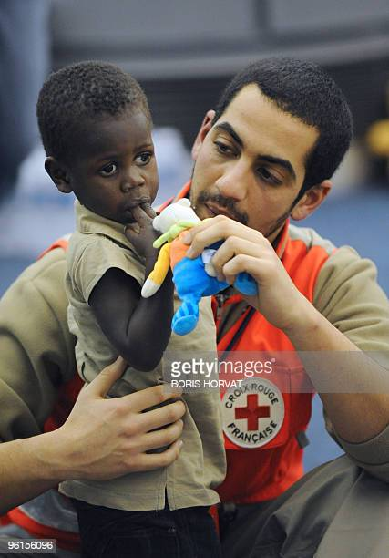 A French Red Cross member tales care of an orphan as she arrives from Haiti at the Roissy airport north of Paris on January 22 2010 A group of 33...