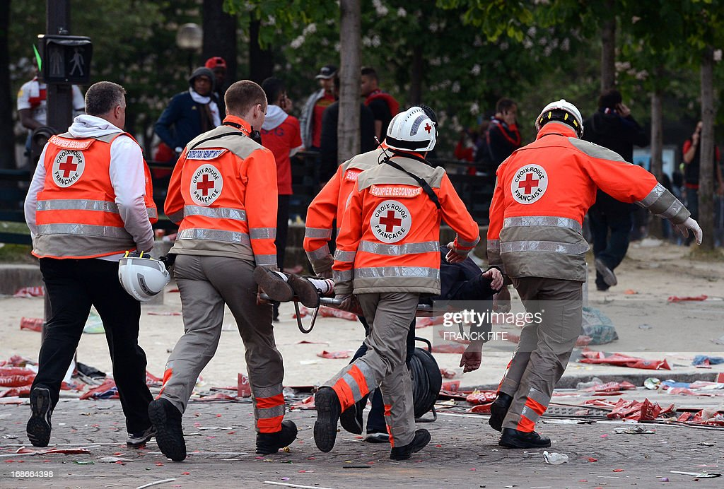 French Red Cross members evacuate a person on a stretcher during clashes with the police as Paris Saint-Germain's supporters celebrate the club's championship on May 13, 2013 in Paris, one day after Paris secured French L1 football championship title.
