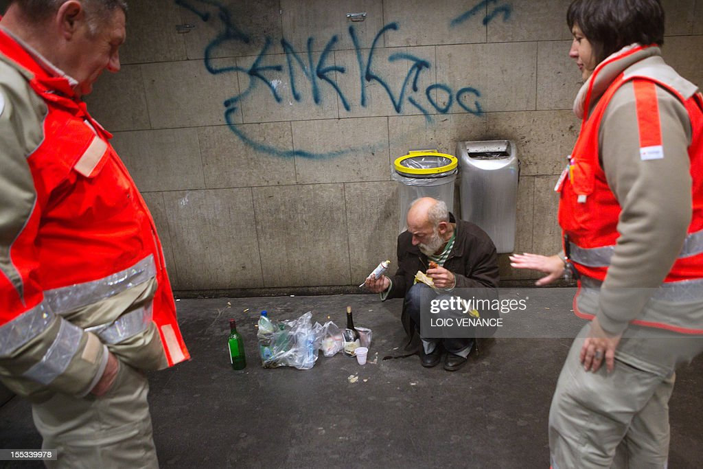 French Red Cross (Croix rouge) volunteers attend to a homeless person in a RER communting train station tunnel, on November 3, 2012 , on November 3, 2012 in Saint-Germain-en-Laye, outside Paris, during a night round of French social Samu (social emergency unit).