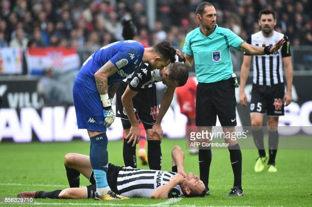 French refere Mikael Lesage gestures during the French L1 football match between Angers and Lyon on October 1 2017 at the RaymondKopa stadium in...