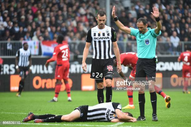 French refere Mikael Lesage gestures next to French defender Romain Thomas during the French L1 football match between Angers and Lyon on October 1...
