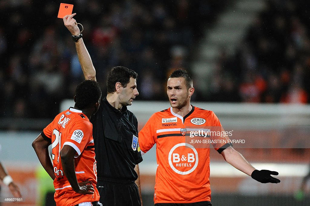 French referee Alexandre Castro gives a red card to Lorient's French midfielder Alain Traore (L) during the French L1 football match between Lorient and Toulouse on February 15, 2014 at the Moustoir stadium in Lorient, western France.