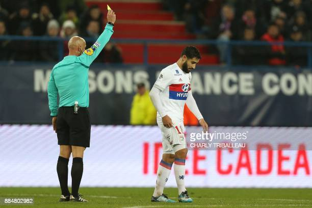 French referee Amaury Delerue gives a yellow card to Lyon's French midfielder Nabil Fekir during the French L1 football match between Caen and Lyon...
