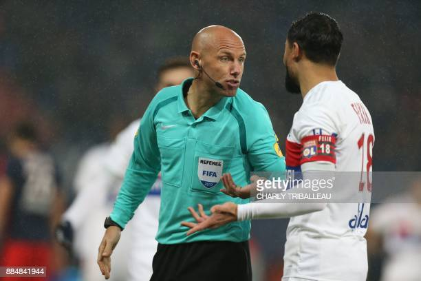 French referee Amaury Delerue speaks to Lyon's French midfielder Nabil Fekir during the French L1 football match between Caen and Lyon on December 3...