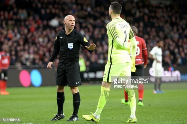 French referee Amaury Delerue talks to Monaco's Croatian goalkeeper Danijel Subasic during the French L1 football match Guingamp vs Monaco on...