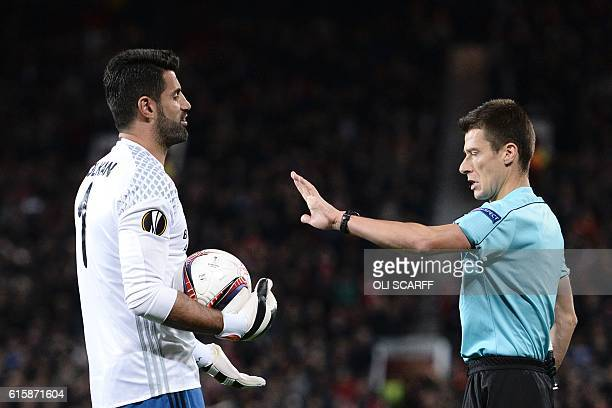 French referee Benoit Bastien gestures to Fenerbahce's Turkish goalkeeper Volkan Demirel during the UEFA Europa League group A football match between...