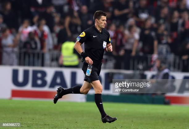 French referee Benoit Bastien runs with a bottle during the French L1 football match Nice vs Marseille on October 01 2017 at the 'Allianz Riviera'...
