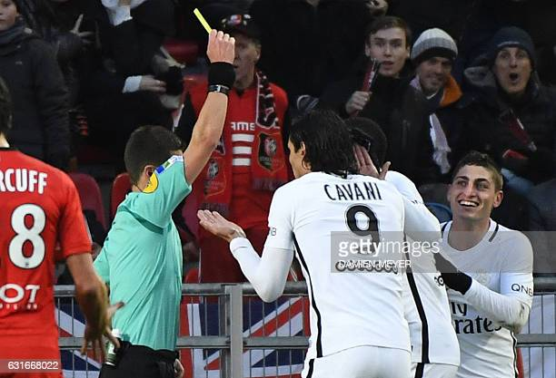 French referee Benoit Bastien shows a yellow card to Paris SaintGermain's Italian midfielder Marco Verratti as his teammate Uruguayan forward Edinson...