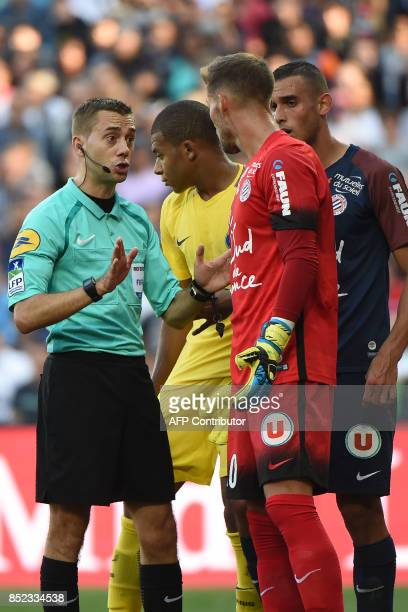 French referee Clement Turpin warns Montpellier's French goalkeeper Benjamin Lecomte as Montpellier's French midfielder Ellyes Skhiri and Paris...
