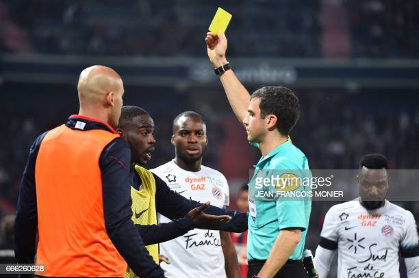 French referee Frank Schneider gives a yellow card to Caen's French defender Alaeddine Yahia and Montpellier's French forward Jonathan Ikone during...