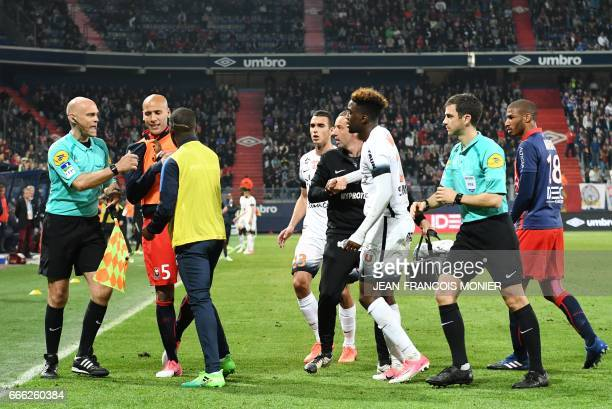French referee Frank Schneider walks and French line referee Nicolas Henninot react as Caen's French defender Alaeddine Yahia and with Montpellier's...