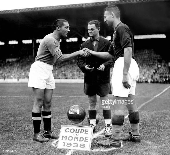 French referee Georges Capdeville looks on as the captains of the Italian and Hungarian national soccer teams Giuseppe Meazza and Gyorgy Sarosi shake...