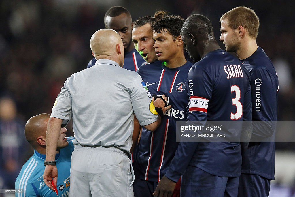 French referee Laurent Duhamel (2ndL) gives a red card to Paris Saint-Germain's Swedish forward Zlatan Ibrahimovic (C) during the French L1 football match Paris Saint-Germain (PSG) vs Saint-Etienne (ASSE) on November 3, 2012 at the Parc des Princes stadium, in Paris. AFP PHOTO KENZO TRIBOUILLARD