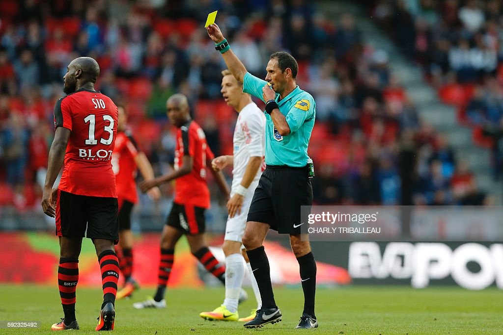 French referee Mikael Lesage gives a yellow card to Rennes' Ivorian forward Giovanni Sio during the French L1 football match between Stade Rennais FC...