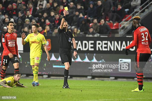 French referee Mikael Lesage shows a yellow card to Rennes' French defender Joris Gnagnon during the French L1 football match Rennes against Nantes...