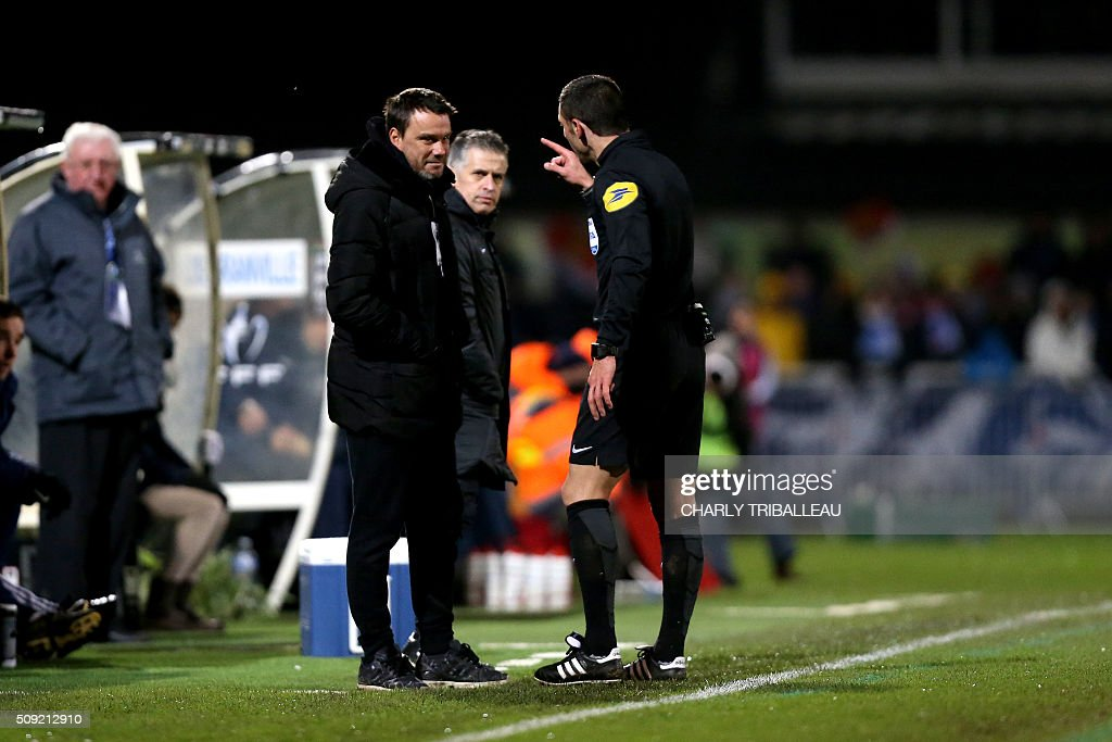 French referee Nicolas Rainville asks to Bourg-en-Bresse headcoach Herve Della Magore to leave the pitch during the French Cup football match between Granville (USG) and Bourg-en-Bresse (FBBP) at the Louis Dior stadium on February 9, 2016 in Granville, northwestern France. AFP PHOTO / CHARLY TRIBALLEAU / AFP / CHARLY TRIBALLEAU