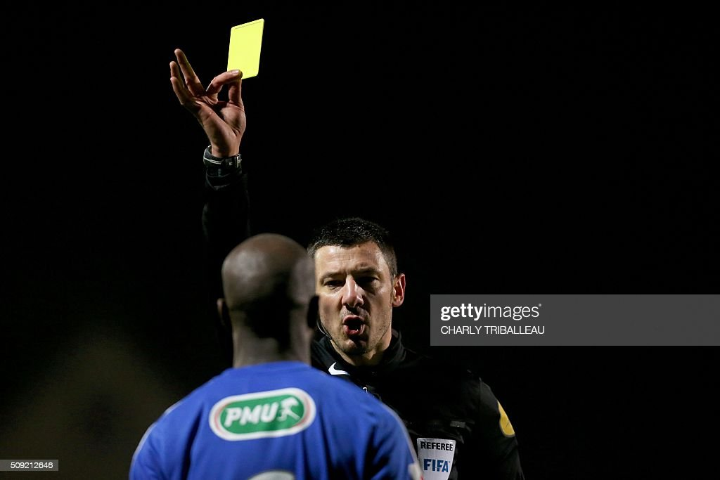 French referee Nicolas Rainville gives a yellow card to Bourg-en-Bresse's midfielder Allou Dembele during the French Cup football match between Granville (USG) and Bourg-en-Bresse (FBBP) at the Louis Dior stadium on February 9, 2016 in Granville, northwestern France. AFP PHOTO / CHARLY TRIBALLEAU / AFP / CHARLY TRIBALLEAU