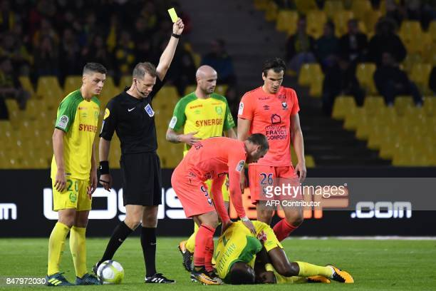 French referee Olivier Thual holds up a yellow card during the French L1 football match between Nantes and Ajaccio on September 16 2017 at Beaujoire...