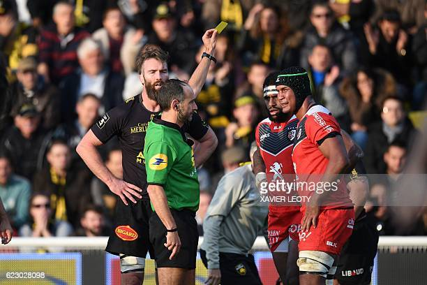 French referee Romain Poite shows a yellow card to Toulouse's Fijian lock Semi Kunatani next to Toulouse's French flanker Thierry Dusautoir during...
