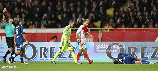 French referee Ruddy Buquet shows a red card to Monaco's French defender Benjamin Mendy after fouling Lyon's French midfielder Corentin Tolisso...