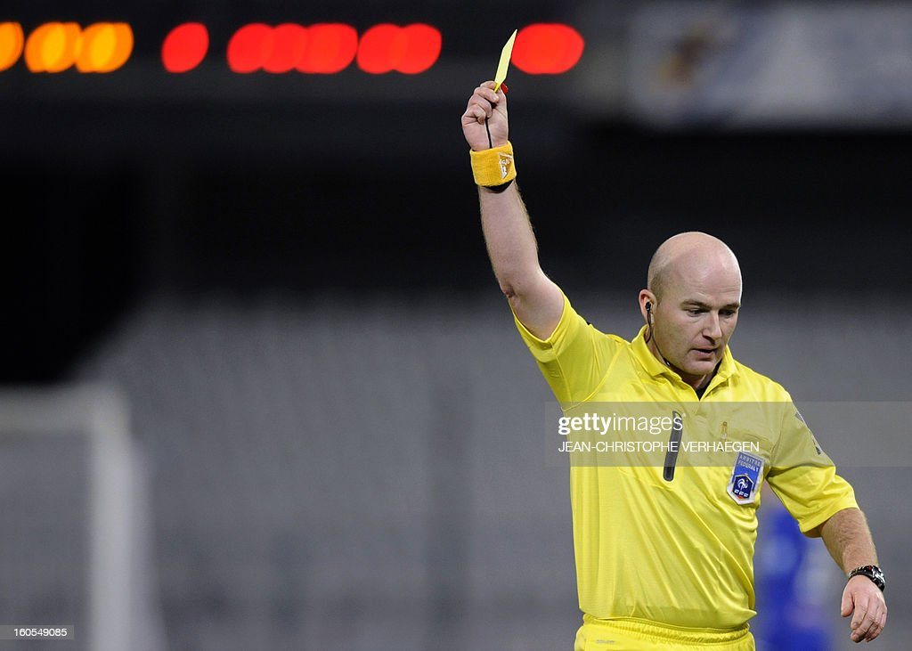 French referee Sebastien Moreira gives a yellow card during the French L1 football match Bastia (SCB) vs Evian (ETGFC) at the Abbe Deschamps Stadium, on February 2, 2013 in Auxerre.