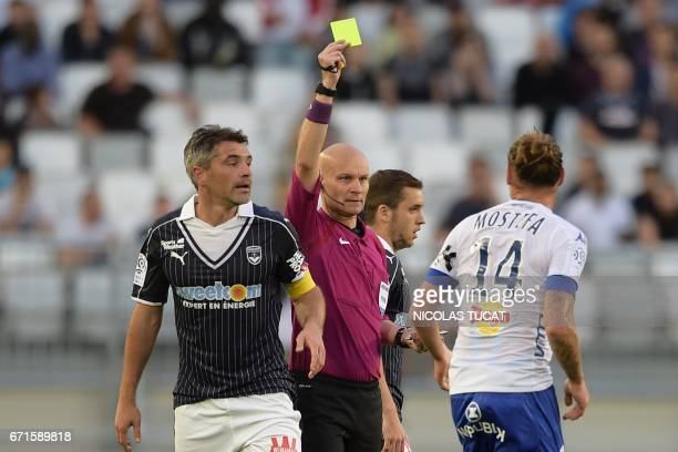 French referee Tony Chapron gives a yellow card to Bastia's Algerian midfielder Mehdi Mostefa during the French L1 football match between Bordeaux...