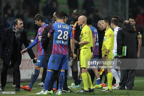 French referee Tony Chapron talks with officials as Len's general manager Xavier Gravelaine looks on after Lens fans used flares causing a game...