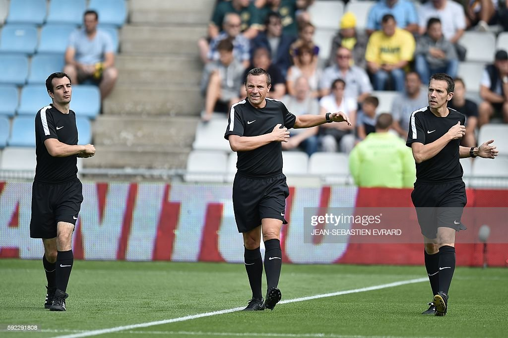 French referees Julien Aube Stephane Lannoy and Philippe Jeanne warm up before the French L1 football match between FC Nantes and AS Monaco on August...