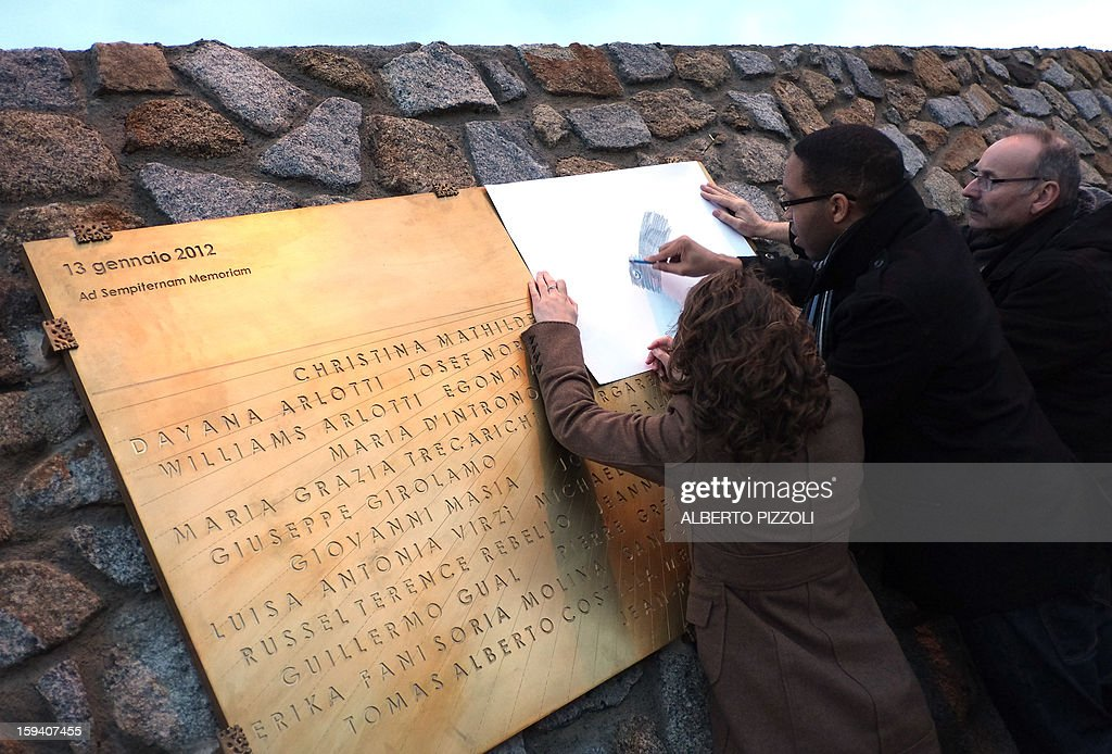 French relatives of Costa Concordia shipwreck's victims trace a name from a commemorative plaque bearing the names of the 32 people who lost their lives in the disaster, on January 13, 2013 on the Italian island of Giglio. Survivors, grieving relatives and locals on the island of Giglio gathered on January 13 to mark the first anniversary of the Costa Concordia cruise ship disaster, which claimed 32 victims.