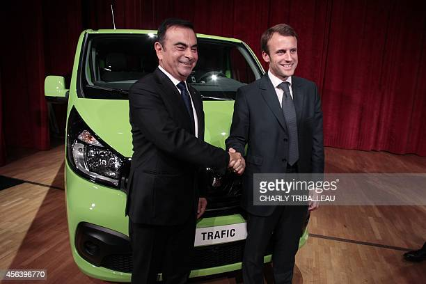 French Renault car maker CEO Carlos Ghosn shakes hands with French Economy Minister Emmanuel Macron in front of a Renault Traffic car during the...