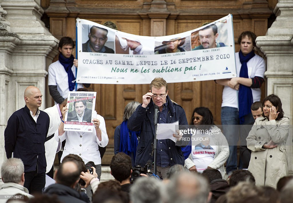 French reporter Herve Ghesquiere, who was held hostage in Afghanistan for 18 months, (C) speaks next to Paris' deputy mayor and socialist candidate to the 2014 municipal elections in Paris Anne Hidalgo (R) in front of the Paris City Hall during a gathering in support of the four French hostages kidnapped in 2010 in the northern Niger town of Arlit to mark their 1000-day captivity on June 22, 2013. The four French nationals -- Pierre Legrand, Daniel Larribe, Thierry Dol and Marc Feret -- were kidnapped on September 16, 2010, by Al-Qaeda in the Islamic Maghreb (AQIM) from the uranium mining town of Arlit, while working for Satom, a subsidiary of the French nuclear group Areva. Sign reads: ''Let's them regain freedom, Pierre Legrand, Marc Feret, Thierry Dolm Daniel Larribe, hostages in Sahel since September 16, 2010, were are not forgetting them''.