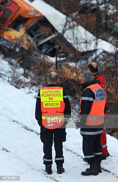 French rescue workers look at the wreckage of a passenger train hit by a massive falling boulder near DignelesBains in the French Alps on February 8...