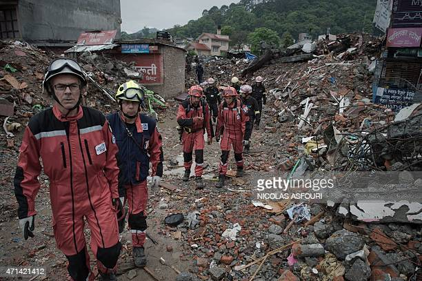French rescue workers walk among earthquake debris as they look for survivors in the Nepalese capital Kathmandu on April 28 2015 Hungry and desperate...