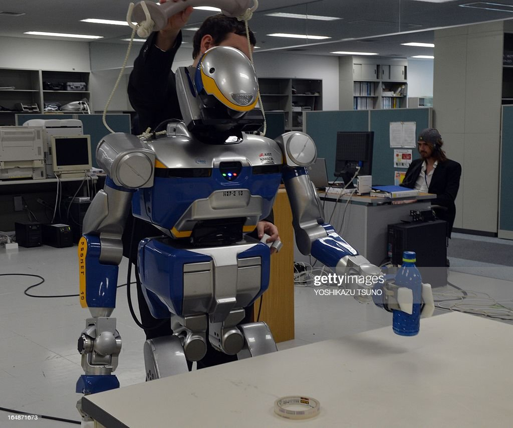 French researchers display a demonstration of a humanoid robot HRP-2, which is controlled by human brain activity with the brain machine interface (BMI) in the Japan-France joint laboratory at the National Institute of Advanced Industrial Science and Technology (AIST) in Tsukuba, suburban Tokyo on March 29, 2013. The HAL, which is designed to learn the user's motion and assist the wearer's movement, can be used for the rehabilitation of disabled and assist elderly people. AFP PHOTO / Yoshikazu TSUNO