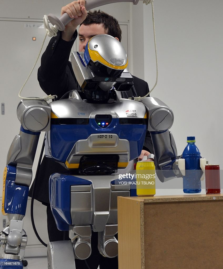 French researchers display a humanoid robot HRP-2, which is controlled by human brain activity with the brain machine interface (BMI) in the Japan-France joint laboratory at the National Institute of Advanced Industrial Science and Technology (AIST) in Tsukuba, suburban Tokyo on March 29, 2013. The HAL, which is designed to learn the user's motion and assist the wearer's movement, can be used for the rehabilitation of disabled and assist elderly people. AFP PHOTO / Yoshikazu TSUNO